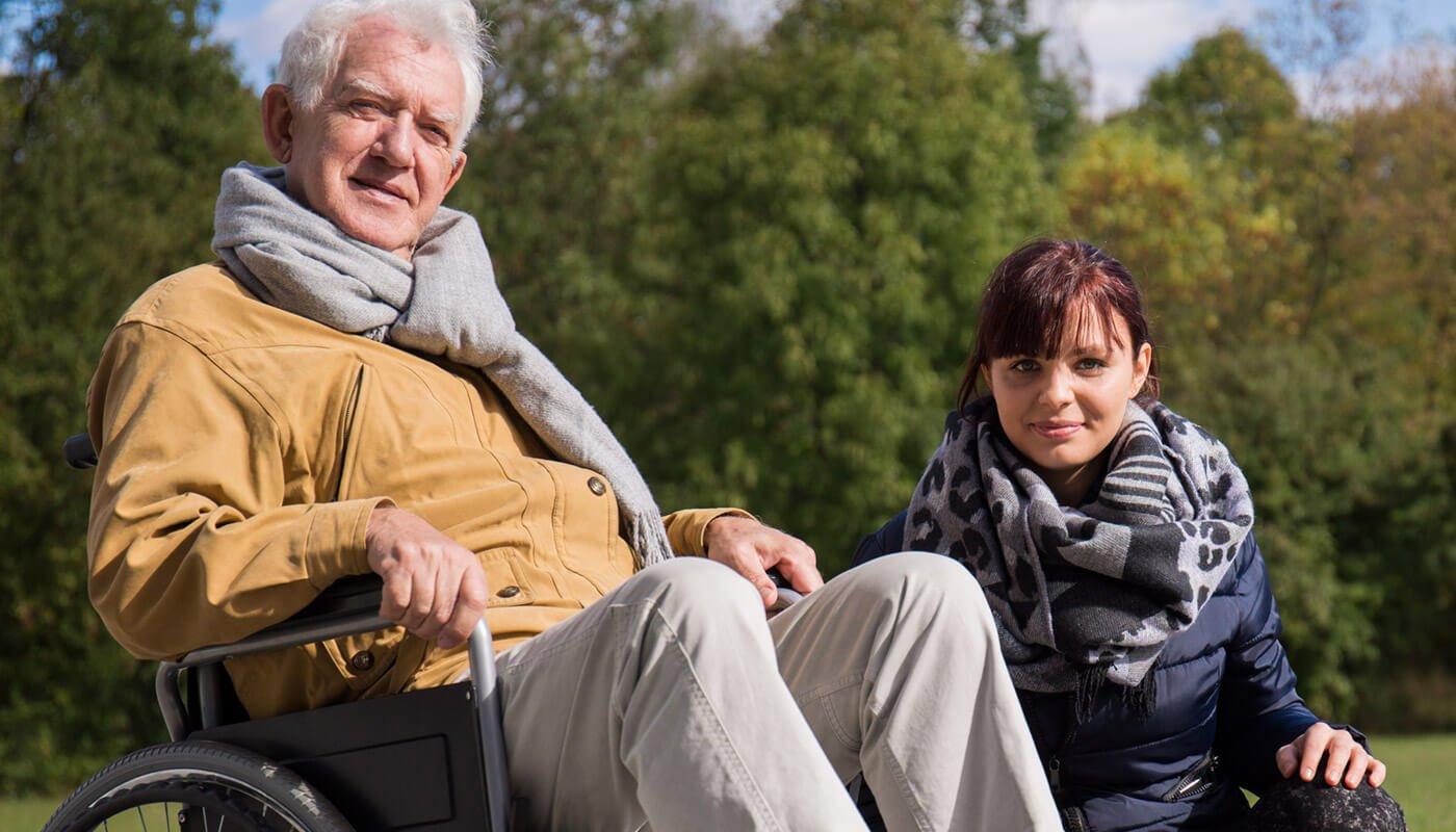 Horizon carer taking wheelchair-bound elderly man for trip outside